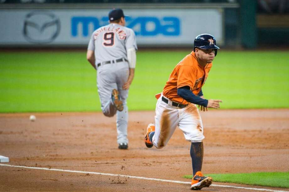 Astros second baseman Jose Altuve races home from third base as the throw gets past Tigers third baseman Nick Castellanos. Photo: Smiley N. Pool, Houston Chronicle