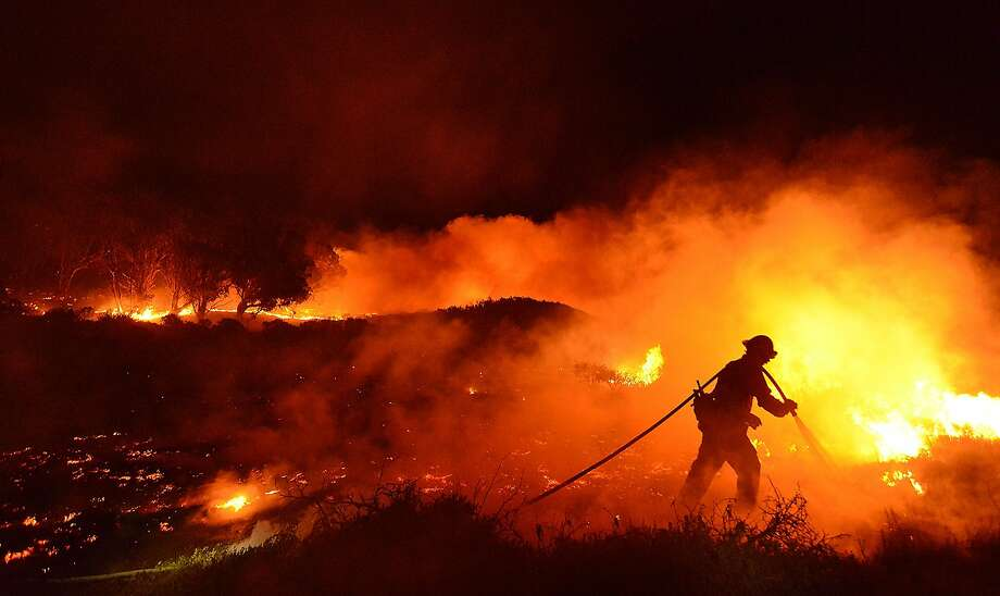 Santa Barbara County Firefighter Chris Hansen douses the western edge of a vegetation fire early Friday morning, June 27, 2014 on UC Santa Barbara's Coal Oil Point Reserve. The 10-15 acre brush fire began Thursday night and the cause is under investigation.  There were no structures damaged. (AP Photo/Santa Barbara County Fire Department, Mike Eliason) Photo: Mike Eliason, Associated Press