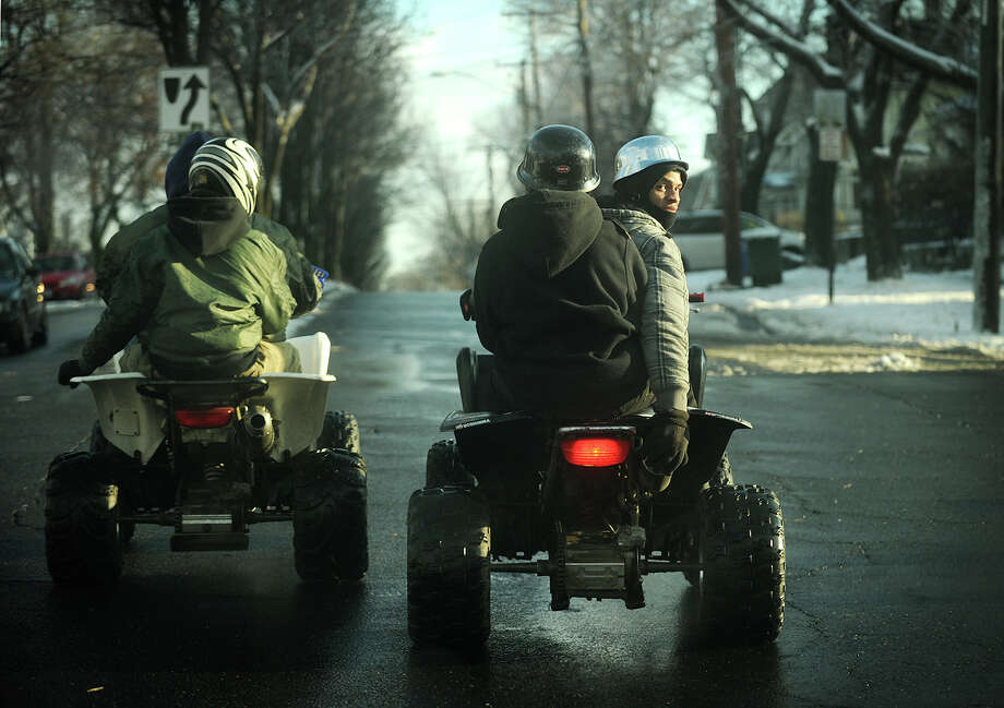 A pair of ATV riders, and their passengers, drive their four wheelers down Park Avenue in Bridgeport, Conn. on Sunday, December 15, 2013. Photo: Brian A. Pounds / Connecticut Post