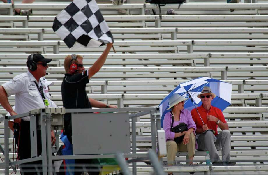 A couple brave the heat while watching a practice session from the grand stands at the Grand Prix of Houston at NRG Park Friday, June 27, 2014, in Houston. Photo: Melissa Phillip, Houston Chronicle / © 2014  Houston Chronicle