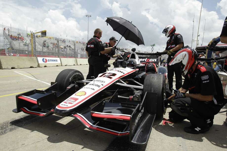 A crew member shades IndyCar driver Will Power with an umbrella during an IndyCar practice session for the Grand Prix of Houston at NRG Park Friday, June 27, 2014, in Houston. Photo: Melissa Phillip, Houston Chronicle / © 2014  Houston Chronicle