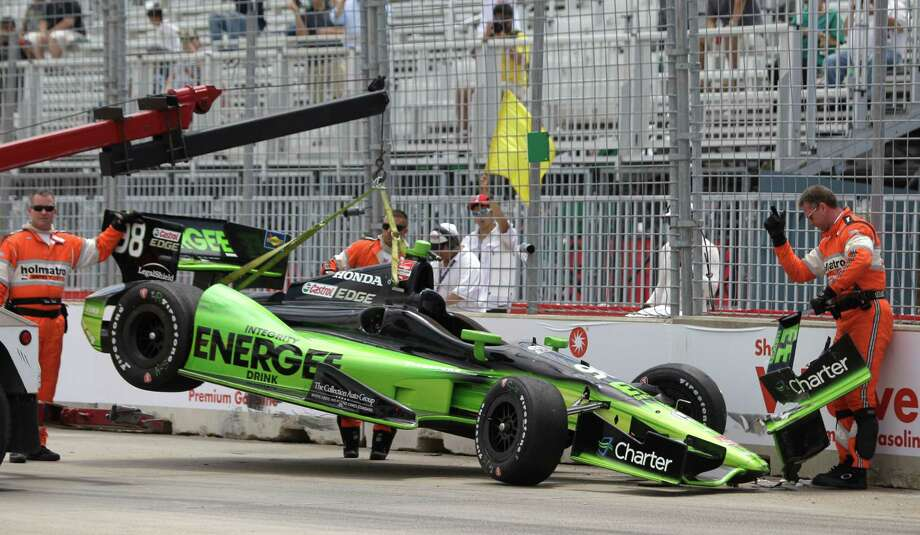 Crews tow the race of car IndyCar driver Jack Hawksworth after his crash near Turn 2 during an IndyCar practice session for the Grand Prix of Houston at NRG Park Friday, June 27, 2014, in Houston. Photo: Melissa Phillip, Houston Chronicle / © 2014  Houston Chronicle