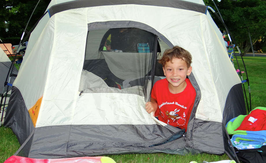 Reid Barry, 7, of Southport, pops out of his tent at Pequot Library's povernight potluck supper and campout Friday evening. Photo: Mike Lauterborn / Fairfield Citizen
