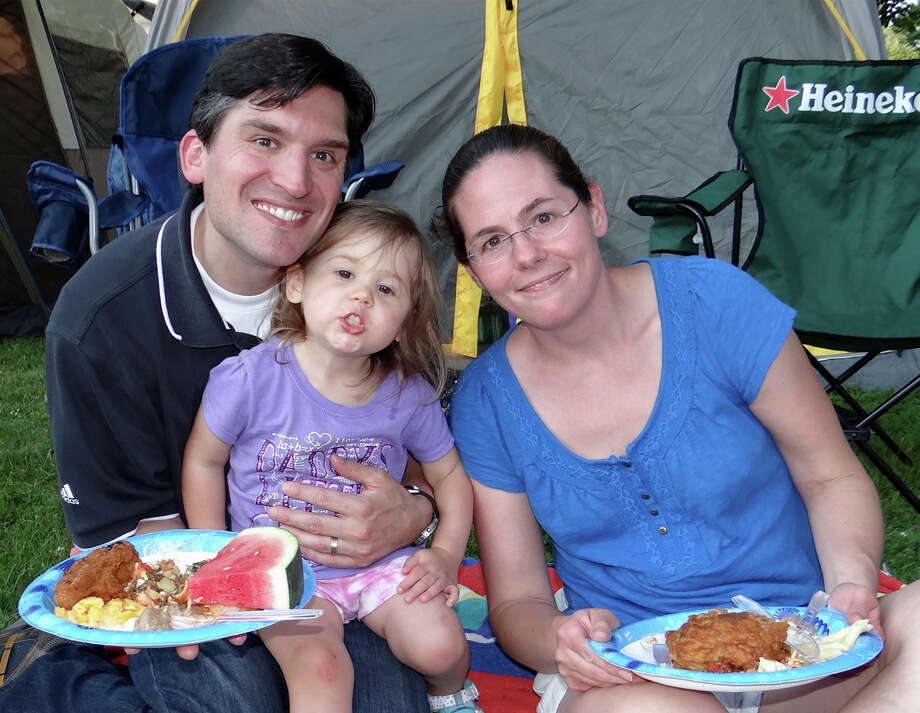 Mike Messina, daughter, Michela, 2, and wife Shannon, of Southport, dine at the Pequot Library's potluck supper and campout Friday evening. Photo: Mike Lauterborn / Fairfield Citizen