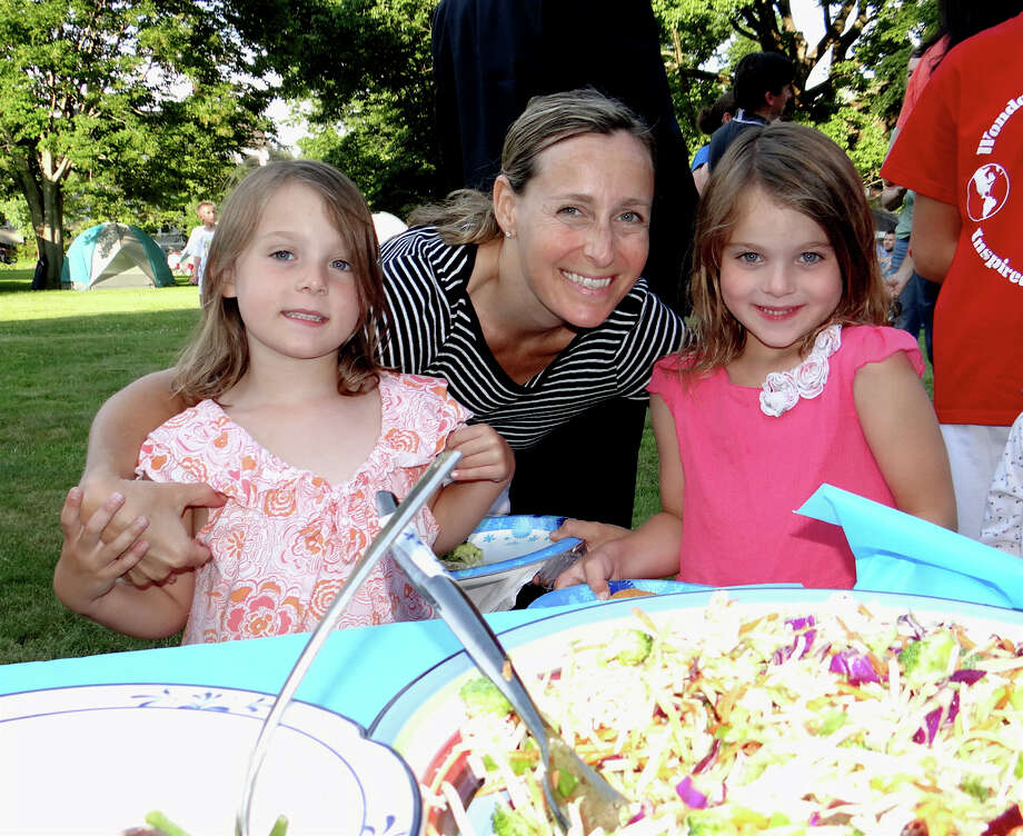 Jen Morgan of Southport and twin daughters, Claire and Paige, 5, get ready to sample the potluck fare at the Pequot Library on Friday evening. Photo: Mike Lauterborn / Fairfield Citizen