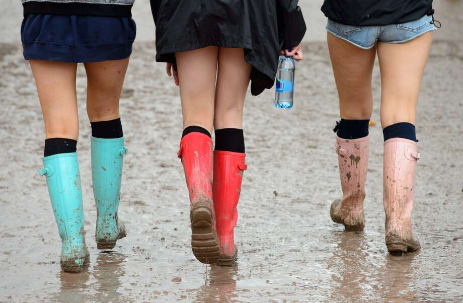 Three festival goers walk through the mud towards the Pyramid stage at the Glastonbury Music Festival, England, Friday, June 27, 2014. Thousands of music fans have arrived for the festival to see headliners Arcade Fire, Metallica and Kasabian. Photo: Jonathan Short, Associated Press