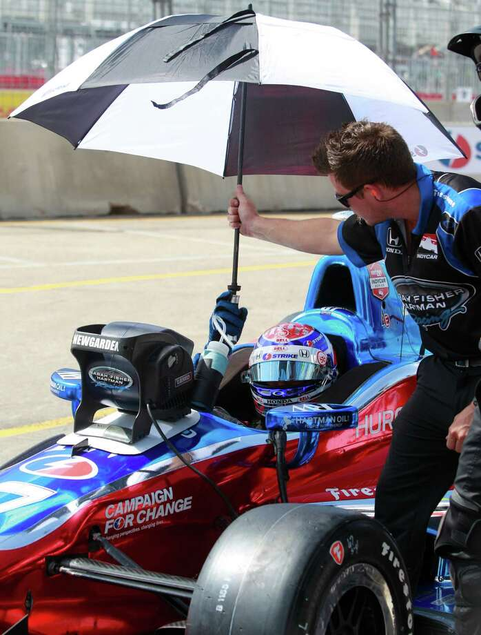 IndyCar driver Josef Newgarden hands an umbrella back to a crew member during an IndyCar qualifying session for the Grand Prix of Houston at NRG Park Saturday, June 28, 2014, in Houston. Photo: Melissa Phillip, Houston Chronicle / © 2014  Houston Chronicle