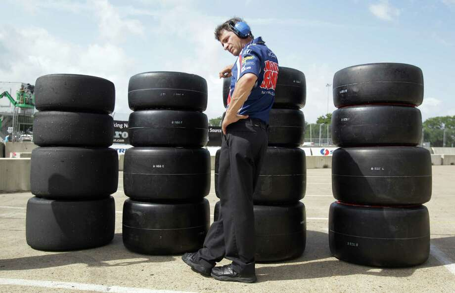 A crew member for IndyCar driver Luca Filippi waits by a stack of tires during an IndyCar qualifying session for the Grand Prix of Houston at NRG Park Saturday, June 28, 2014, in Houston. Photo: Melissa Phillip, Houston Chronicle / © 2014  Houston Chronicle