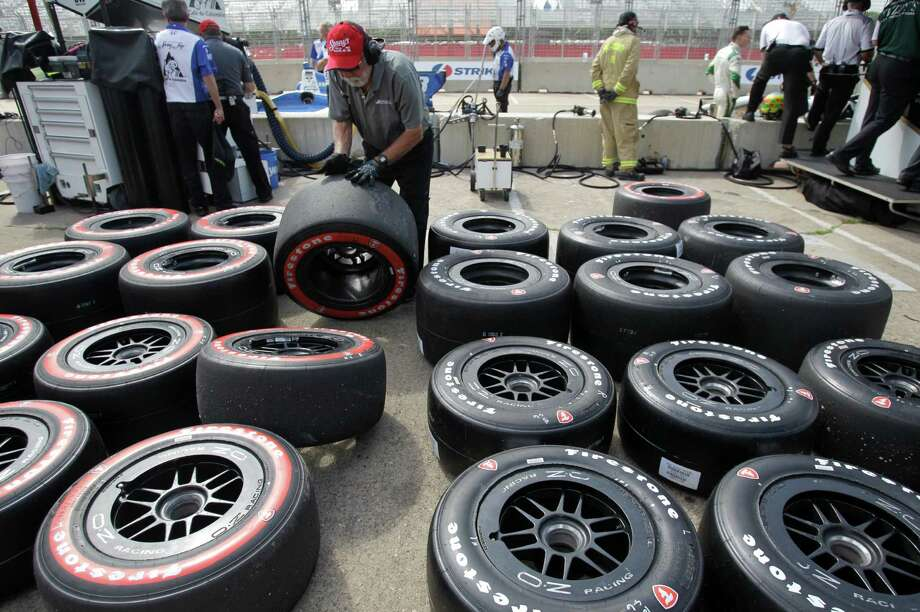 A IndyCar team crew member moves tires during an IndyCar qualifying session for the Grand Prix of Houston at NRG Park Saturday, June 28, 2014, in Houston. Photo: Melissa Phillip, Houston Chronicle / © 2014  Houston Chronicle