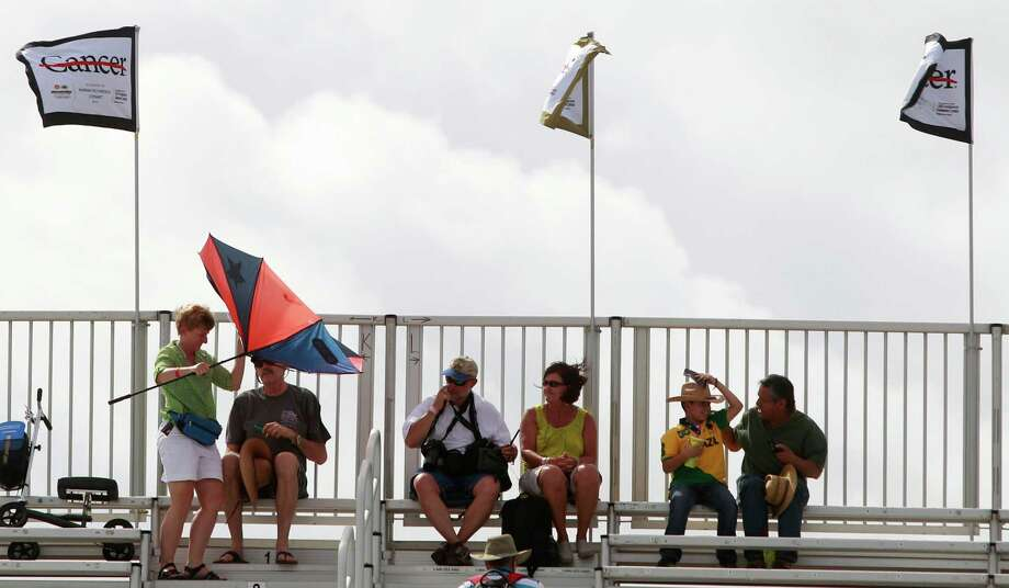 Fans brave the wind and heat while watching  an IndyCar qualifying session for the Grand Prix of Houston at NRG Park Saturday, June 28, 2014, in Houston. Photo: Melissa Phillip, Houston Chronicle / © 2014  Houston Chronicle