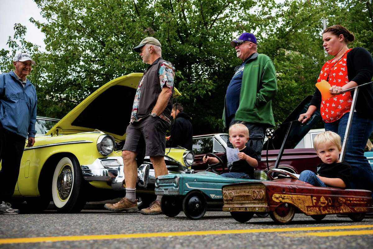 A couple of little tykes are pushed through the annual Greenwood Car Show in miniature versions of famous classic vehicles Saturday, June 28, 2014, in Seattle, Wash.