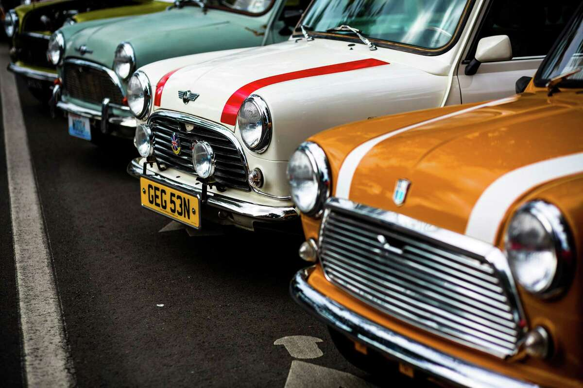 A line of colorful Mini Coopers at the annual Greenwood Car Show Saturday, June 28, 2014, in Seattle, Wash.