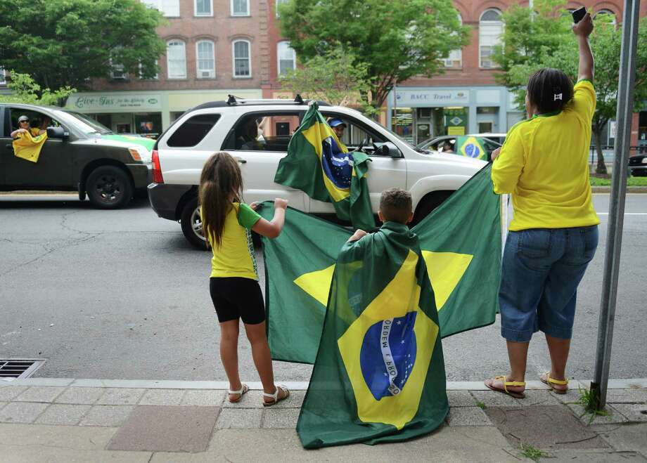 Laryssa, 5, Luan, 3, and Josiane Andrade, of Danbury, celebrate on Main Street in Danbury, Conn. after Brazil's 3-2 World Cup soccer win over Chile Saturday, June 28, 2014.  Brazil and Chile were tied 1-1 at the end of regulation, but won 3-2 on penatly kicks. Photo: Tyler Sizemore / The News-Times