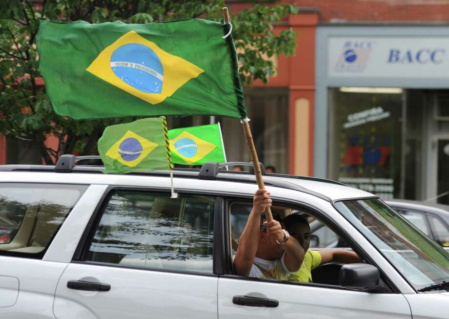 Fans celebrate on Main Street in Danbury, Conn. after Brazil's 3-2 World Cup soccer win over Chile Saturday, June 28, 2014.  Brazil and Chile were tied 1-1 at the end of regulation, but won 3-2 on penatly kicks. Photo: Tyler Sizemore / The News-Times