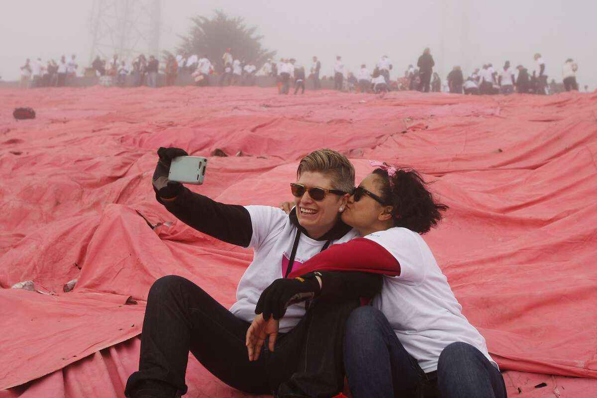 Raffaella Wilson, left, and Melanie Buntichai pose for a selfie along the slope of Twin Peaks after the construction of the pink tarp on June 28, 2014 in San Francisco, CA. The Pink Triangle, symbol of the oppression of LGBT people, was built on Twin Peaks Saturday in recognition of the pride celebration.