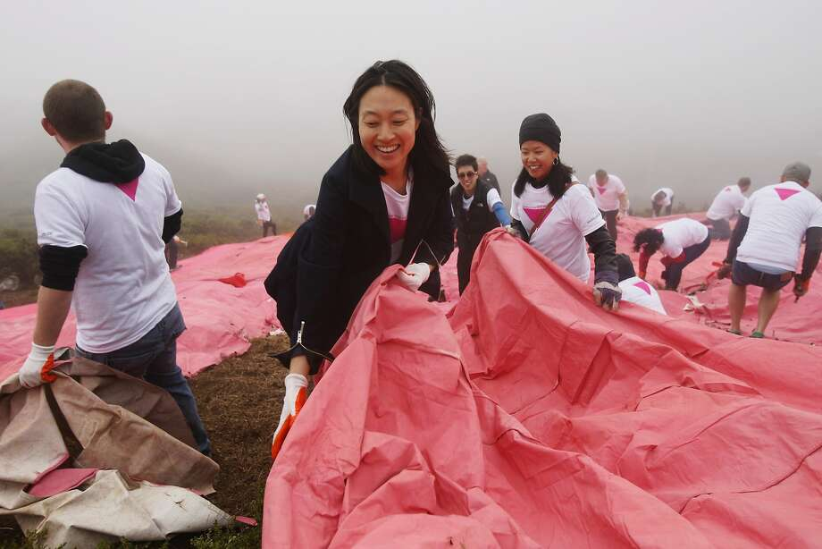 Meyeon Park helps spread out a pink tarp along the slope of Twin Peaks on June 28, 2014 in San Francisco, CA. The Pink Triangle, symbol of the oppression of LGBT people, was built on Twin Peaks Saturday in recognition of the pride celebration. Photo: Craig Hudson, The Chronicle