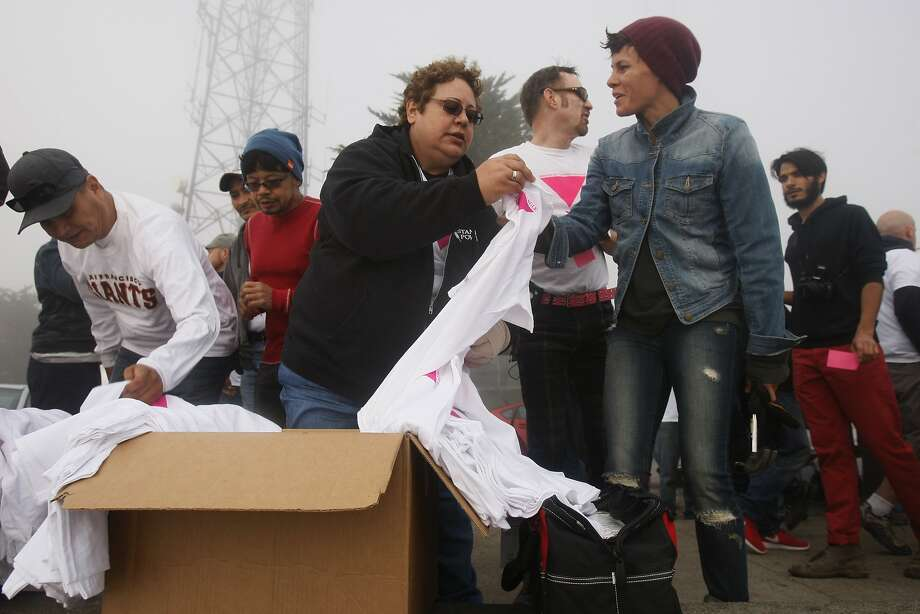 Tina Vieira hands out materials to volunteers at the beginning of the construction of the pink triangle at Twin Peaks on June 28, 2014 in San Francisco, CA. The Pink Triangle, symbol of the oppression of LGBT people, was built on Twin Peaks Saturday in recognition of the pride celebration. Photo: Craig Hudson, The Chronicle