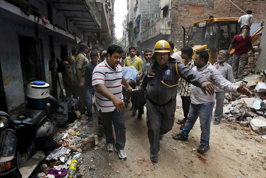 Rescuers carry the body of a victim amid the debris of a dilapidated building that collapsed in New Delhi. Hours later, a building under construction collapsed on the outskirts of Chennai. Photo: Altaf Qadri, Associated Press