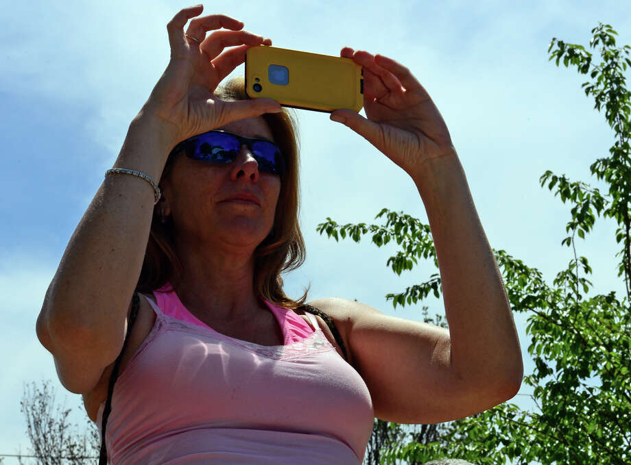 Wendy Wolfe, of Milford, takes photos during the Milford Volunteers Ancient Fife & Drum Corps 50th Anniversary Muster and Parade which was held along Broad Street at the historic Milford Green in downtown Milford on Saturday June 28, 2014. The event coincides with the 375th anniversary celebrations for the founding of Milford going on throughout the summer. Photo: Christian Abraham / Connecticut Post