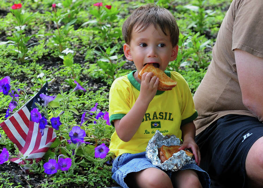 Xander Bach, 3, of Milford, enjoys a sandwich during the Milford Volunteers Ancient Fife & Drum Corps 50th Anniversary Muster and Parade which was held along Broad Street at the historic Milford Green in downtown Milford on Saturday June 28, 2014. The event coincides with the 375th anniversary celebrations for the founding of Milford going on throughout the summer. Photo: Christian Abraham / Connecticut Post
