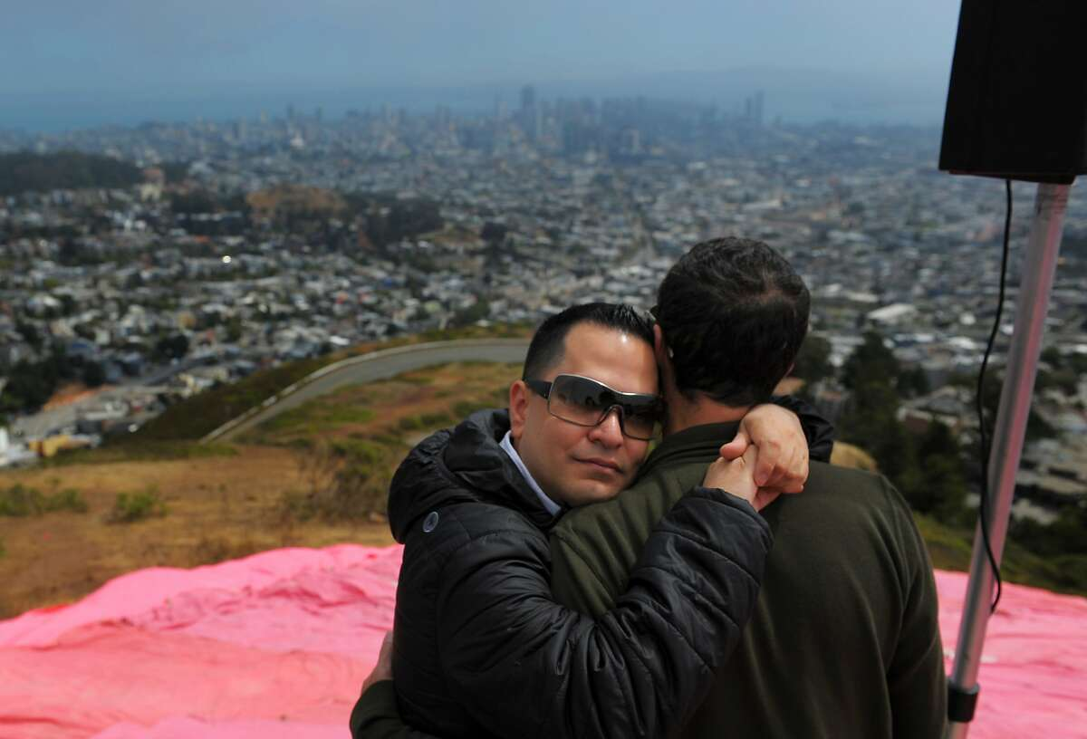Bill Gardnev embraces Joe Lesca above the pink triangle at Twin Peaks on June 28, 2014 in San Francisco, CA. The Pink Triangle, symbol of the oppression of LGBT people, was built on Twin Peaks Saturday in recognition of the pride celebration.