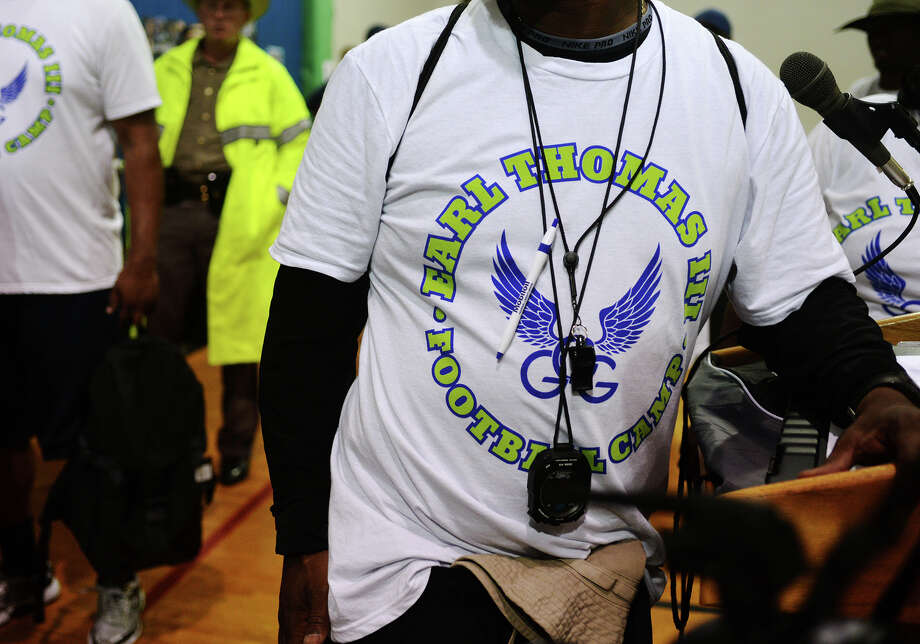 A coach wears an Earl Thomas III Football Camp shirt Friday morning. Seattle Seahawks safety and graduate of West Orange-Stark High School Earl Thomas III hosted his annual football camp at West Orange-Stark starting Friday morning. Thomas also recruited the help of several other NFL players for the camp. Photo taken Friday 6/27/14 Jake Daniels/@JakeD_in_SETX Photo: Jake Daniels / ©2014 The Beaumont Enterprise/Jake Daniels