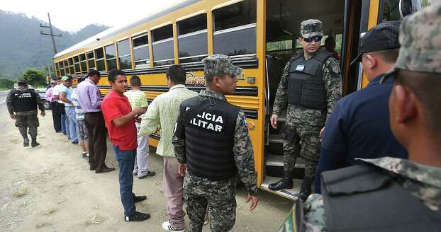 Captain Carlos Madrid, right, of the Honduras Military Police prepares to check identification papers of women on a bus traveling to Guatemala, as the men passengers line up to be searched, near the border town of Corinto, Honduras. Friday, June 27, 2014. Photo: Bob Owen, San Antonio Express-News / ©2013 San Antonio Express-News
