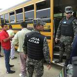 Captain Carlos Madrid, right, of the Honduras Military Police prepares to check identification papers of women on a bus traveling to Guatemala, as the men passengers line up to be searched, near the border town of Corinto, Honduras. Friday, June 27, 2014.