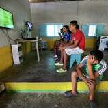Teenage boys play soccer video games in the back room of a small snack store in Corinto, Honduras at the Guatemala border. Friday, June 27, 2014. The sparsely populated area is know for human and drug trafficking with many hidden crossing points into Guatemala.