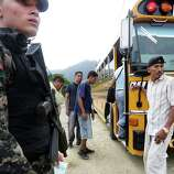 A Military Police officer stands guard as passengers re-board a bus on its' way to Guatemala after being checked for authorized papers near Corinto, Honduras at the Guatemala border. Friday, June 27, 2014.