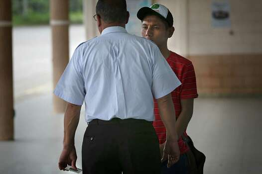 Lluis Hernandez, right, 19, who was turned away at the Guatemala border for being a minor, pleads his case to an immigtation officer at the Immigration Office in Honduras at the Guatemala border. Friday, June 27, 2014.  The officer walked him away from the immigration office towards the small town of Corinto, and the young man wasn't seen again.  Corinto is known for hidden crossing points going into Guatemala undetected. Photo: Bob Owen, San Antonio Express-News / ©2013 San Antonio Express-News