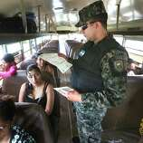 Captain Carlos Madrid of the Honduras Military Police checks the identification papers of a Honduran woman traveling with her two children to Guatemala, near the border town of Corinto, Honduras. One child was born in Honduras and the other was born in Guatemala, and they were allowed to pass. Friday, June 27, 2014.