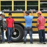 Male bus passengers are searched by Honduran Military Police at a military check point near Corinto, Honduras at the Guatemala border. They were allowed to pass but still had to present papers to immigration at the border.  Friday, June 27, 2014.