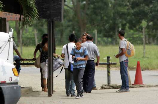 Evin Salvapena, center, walks away from the check point at the Guatemalan border near Corinto, Honduras, for being underage and traveling without permission from his parents. Friday, June 27, 2014. The man in the white shirt, who claimed to be Salvapena's cousin, argues his point with a Guatemalan border official. Photo: Bob Owen, San Antonio Express-News / ©2013 San Antonio Express-News