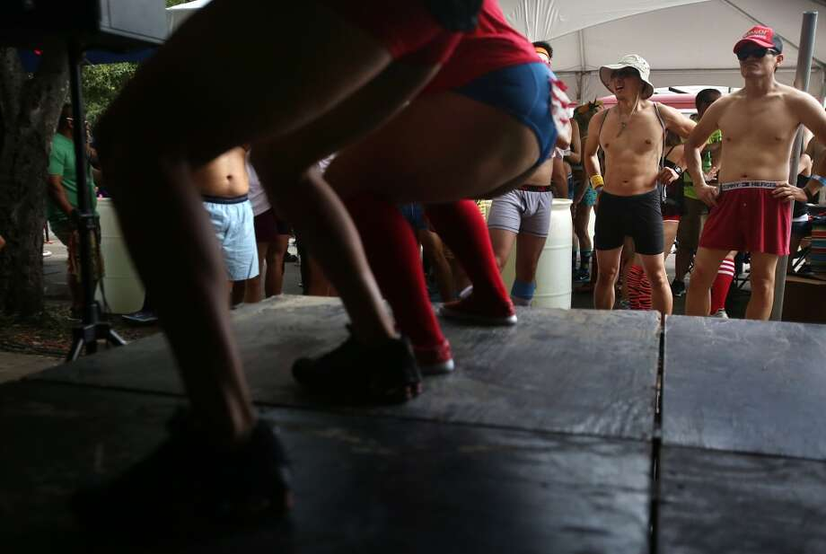 Runners view people dancing during the pre-party to the Hot Undies Run on June 28, 2014, in Houston, Tx. The Hot Undies Run charity event started at the Gorgeous Gael Pub in Rice Village. ( Mayra Beltran / Houston Chronicle ) Photo: Houston Chronicle