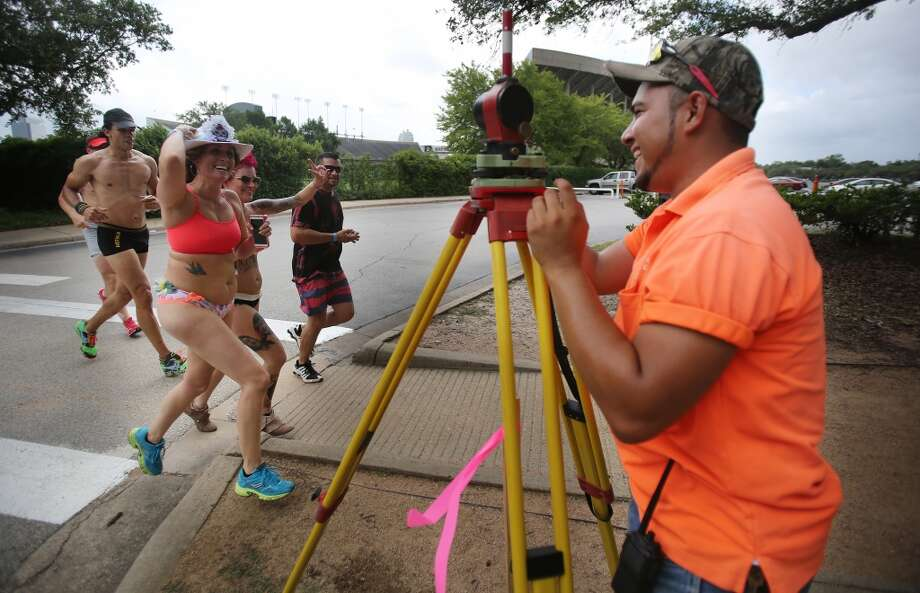 """I can't get any work done with my wondering eye"" says  John Valdez while trying to finish his land surveying work and as participants jog along Rice Blvd. during the Hot Undies Run on June 28, 2014, in Houston, Tx. The Hot Undies Run charity event started at the Gorgeous Gael Pub in Rice Village. ( Mayra Beltran / Houston Chronicle ) Photo: Houston Chronicle"