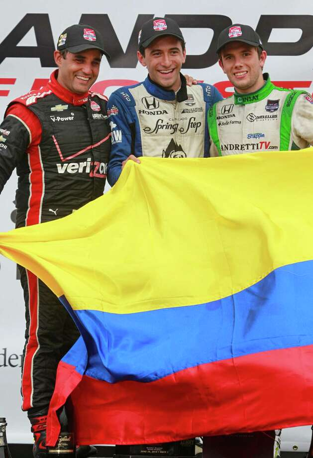 IndyCar drivers Juan Pablo Montoya, left, second place finisher, Carlos Huertas, center, first place finisher, and Carlos Munoz, right, third place finisher, pose with the Columbian flag as they celebrate after the IndyCar Series Race #1 at the Grand Prix of Houston at NRG Park Saturday, June 28, 2014, in Houston. Photo: Melissa Phillip, Houston Chronicle / © 2014  Houston Chronicle