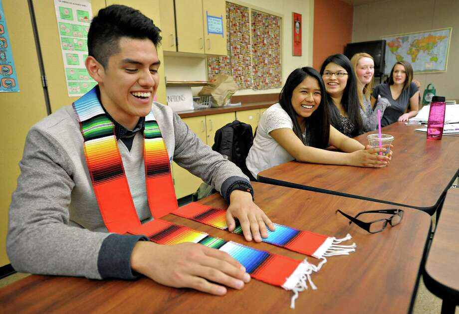 Corvallis (Ore.) High School bilingual student Eduardo Ramirez tries out the stole he and his classmates were to wear at graduation this month. Photo: Andy Cripe, MBR / The Gazette-Times