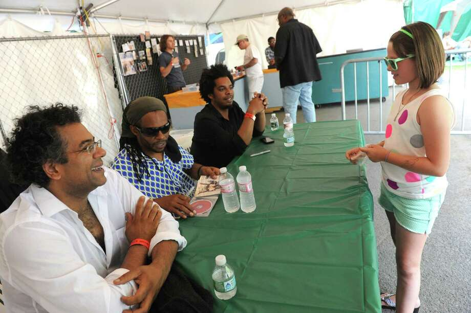Nine-year-old Natalie Baxter, right, of Johnstown gets a cd autographed by The Marc Cary, center, Focus Trio featuring Rashaan Carter, right end of table, and Sameer Gupta, left, following theirperformance on the gazebo stage during the 2014 Freihofer's Saratoga Jazz Festival  on Saturday June 28, 2014 in Saratoga Springs, N.Y. (Michael P. Farrell/Times Union) Photo: Michael P. Farrell / 00027434A