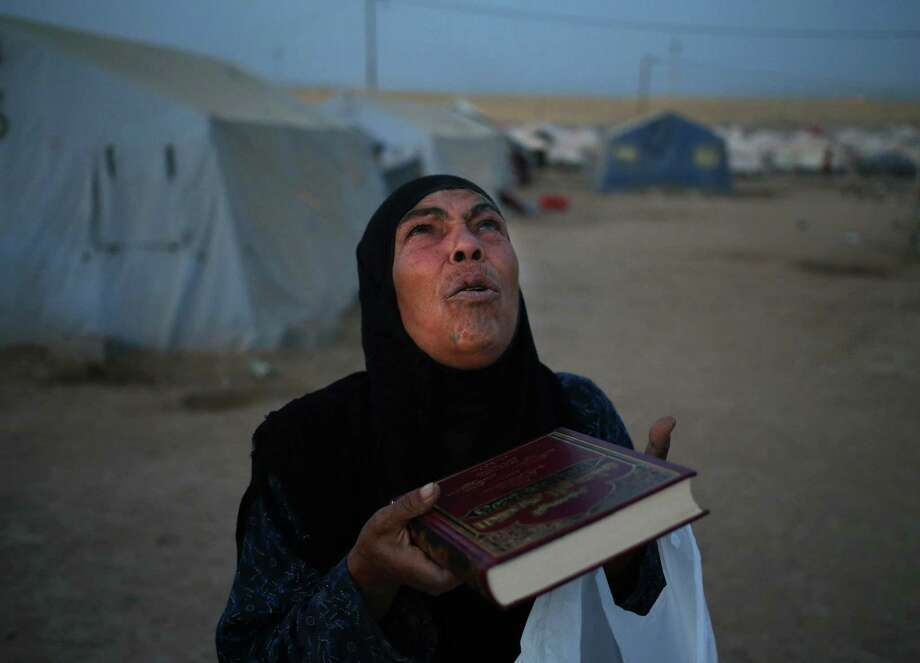 A displaced Iraqi woman who fled with her family from the Iraqi city of Mosul prays after receiving a copy of the Quran from a Kurdish charity on Saturday as Ramadan started. Photo: Hussein Malla, STF / AP