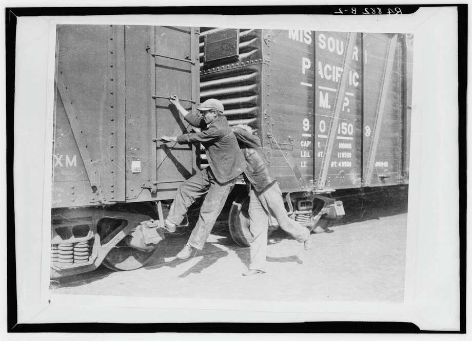 Boys hop a freight train sometime between 1925 and 1935, much like Joe Holley's father did, while looking for farm work just before the Great Depression. / Library of Congress