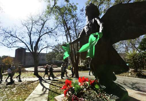 Green ribbons are attached to the hands of an angel statue at The University of the Incarnate Word where a memorial service for Robert Cameron Redus was held.  Friends and family members of Redus, walking by, are going to a tree planting for Redus. Monday, Jan. 13, 2013. Photo: BOB OWEN, San Antonio Express-News / © 2012 San Antonio Express-News