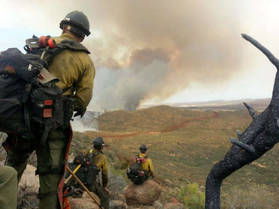 FILE - In this Sunday, June 30, 2013 file photo made by firefighter Andrew Ashcraft, members of the Granite Mountain Hotshots watch a growing wildfire that later swept over and killed the crew of 19 firefighters near Yarnell, Ariz.  Ashcraft texted the photo to his wife, Juliann, but died later that day battling the out-of-control blaze. One year after the 19 Arizona firefighters were killed in the worst loss of life among wildland firefighters in 80 years, few changes have been implemented among the state's fire crews. (AP Photo/Courtesy of Juliann Ashcraft, File) Photo: Andrew Ashcraft, HONS / Juliann Ashcraft
