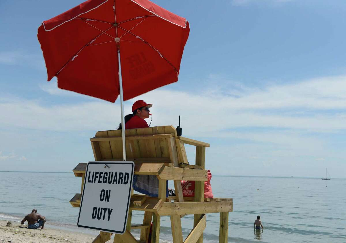 Lifeguard Nicole Cotto keeps watch over Pleasure Beach in Bridgeport, Conn., Saturday, June 28, 2014, the first day of the park's reopening.