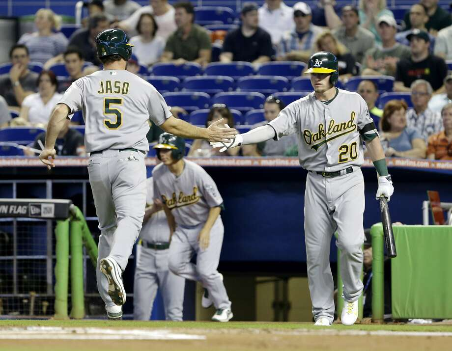 Oakland Athletics' John Jaso (5) is congratulated by Josh Donaldson (20) after Jaso and Coco Crisp (not shown) scored on a single by Brandon Moss during the first inning of a baseball game against the Miami Marlins, Saturday, June 28, 2014, in Miami. (AP Photo/Wilfredo Lee) Photo: Wilfredo Lee, Associated Press