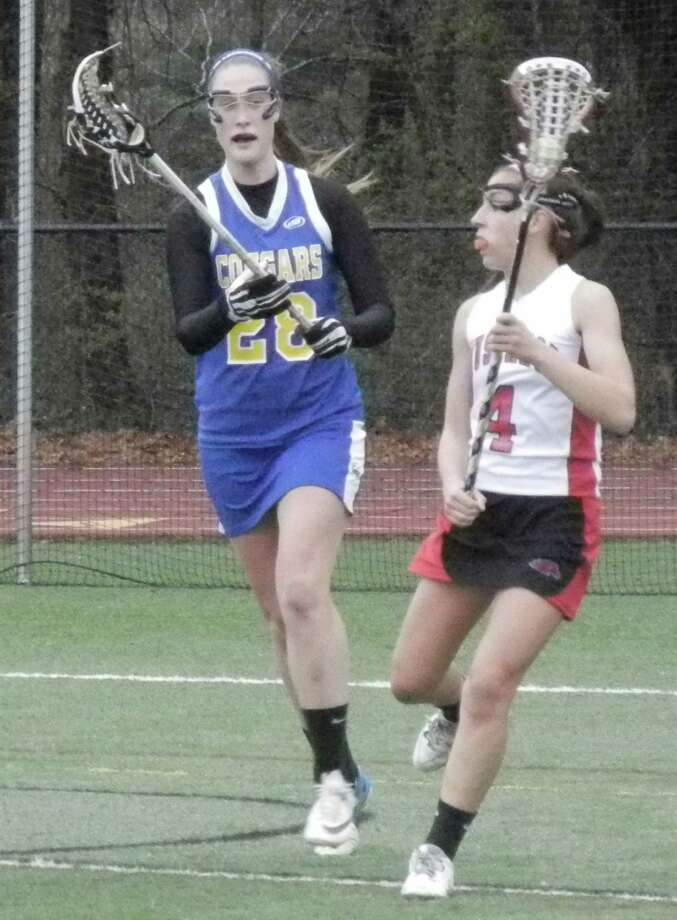 Fairfield Warde junior Sarah Reilly guarded by Haddam-Killingworth's Kathryn Hausherr on Saturday, April 26 in a non-conference girls lacrosse game at Tetreau/Davis Field. Reilly scored five goals in the Mustangs' 14-1 victory. Photo: Reid L. Walmark / Fairfield Citizen