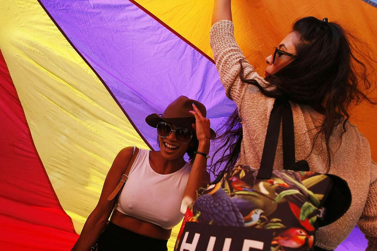 Nina Reyez, left, laughs as she walks under a rainbow parachute before the Dyke March in San Francisco, Calif. on Saturday, June 28, 2014. The annual Dyke March featured live music and a parade through the Mission.