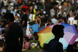 A woman is silhouetted by a Rainbow Umbrella before the Dyke March in San Francisco, Calif. on Saturday, June 28, 2014. The annual Dyke March featured live music and a parade through the Mission.