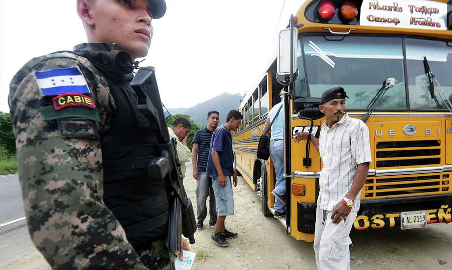 A military police officer stands guard last week as passengers reboard a bus on its way to Guatemala after being checked for authorized papers near Corinto, Honduras, at the Guatemala border. Photo: Bob Owen, Staff / ©2013 San Antonio Express-News