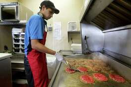 Collin Lybarger tends to burgers on the grill at the Dairy Queen in Karnes City, TX, where they have seen an increase of business due to the oil and gas industry in the area, Thursday, August 29, 2013. Some days they get an order for over 100 burgers to go.